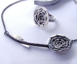 A photo of a metal hand crafted rose necklace and ring