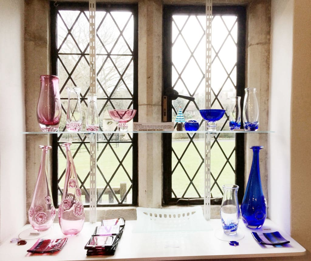 A photo of a window with blue and pink glass vases on the windowsill