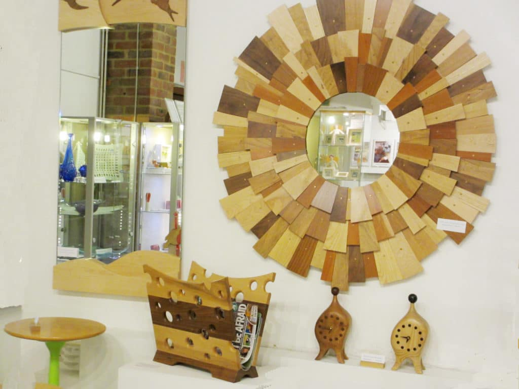 A photo of A wooden mirror, wooden clocks and wooden magazine rack